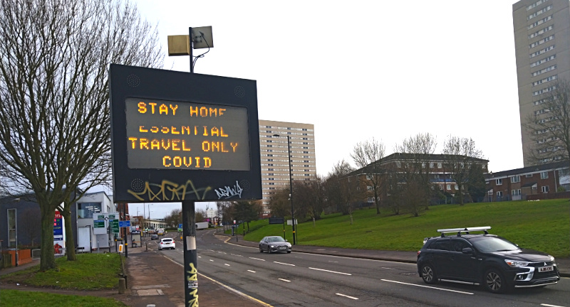 A roadsign in Birmingham reading 'Stay Home, Essential Travel Only, Covid'